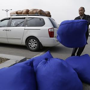 A South Korean man unload sacks full of his company's products upon arrival back from North Korea's Kaesong (AP)