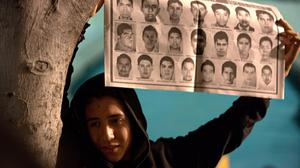 A protester holds a poster with portraits of some of the 43 missing students during a massive march in Mexico City (AP)