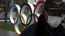 A security guard walks past the Olympic rings near the New National Stadium in Tokyo (AP)