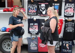 An armed woman sells Trump merchandise outside the rally
