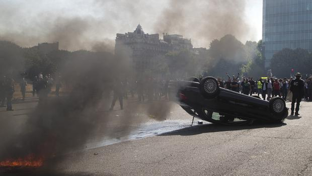 Striking taxi drivers stand behind an overthrown car during a demonstration in Paris (AP)