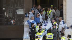 Israeli rescue workers carry a body from the scene of a shooting attack in a synagogue in Jerusalem (AP)