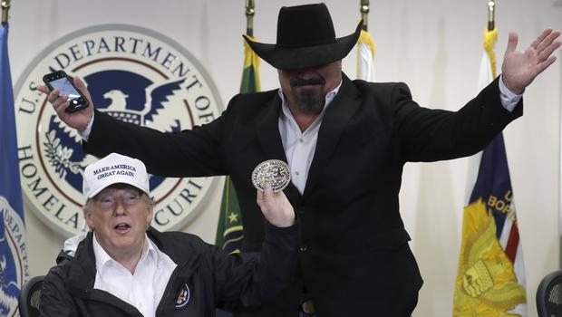 President Donald Trump holds up a belt buckle given to him to by rancher Monty Awbrey (Evan Vucci/AP)