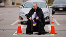 A priest hears drive-up confessions in a church car park in Massachusetts. Photo: Brian Snyder/Reuters