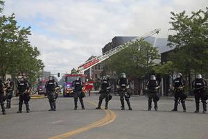 Minnesota state troopers provide protection as firefighters battle a blaze (Jim Mone/AP)