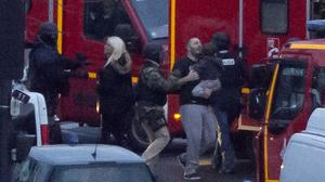 A security officer directs released hostages after they stormed a kosher market to end a hostage situation in Paris (AP)