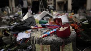 Pencils, candles, and flowers are set up next to Charlie Hebdo newspaper in Paris (AP)