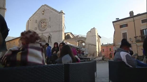 Residents who fled from their houses gather in a square in front of a damaged church in Norcia, Italy (Sky Italia via AP)
