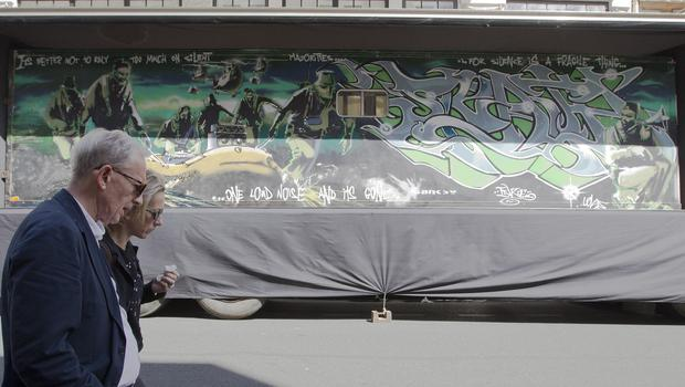 """People walk past a trailer which street artist Banksy turned into a piece entitled """"Silent Majority"""". (AP)"""