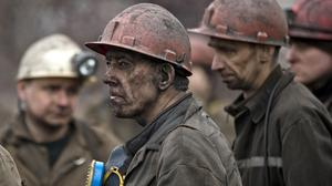Ukrainian coal miners wait for a bus after returning to the surface of the Zasyadko mine in Donetsk (AP)