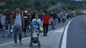 Migrants walk in a long line along the highway near Budapest, Hungary. (AP)