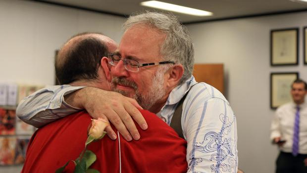 Christopher Brown, left, and Tom Fennell hug after getting their marriage license at the Douglas County County Clerk's office in Omaha, Nebraska (AP)