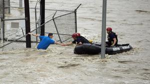 Rescuers grab the hand of a man stranded in rushing water in Austin, Texas (Alberto Martinez/Austin American-Statesman via AP)