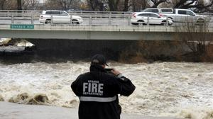 A Sparks firefighter takes a photo of the rising Truckee River (AP/Scott Sonner)