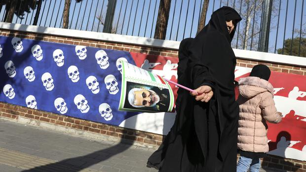 A mourner holds a poster of Iranian General Qassem Soleimani as she passes a satirical US flag after a ceremony for the general and colleagues killed in Iraq in a US drone attack (Vahid Salemi/AP)