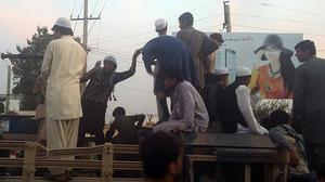 Taliban fighters and young men take over an army truck on a street in Kunduz, Afghanistan (AP)