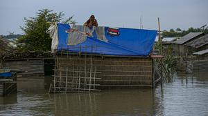An Indian woman stands on the roof of her partially submerged house along the River Brahmaputra in Assam, India (Anupam Nath/AP)