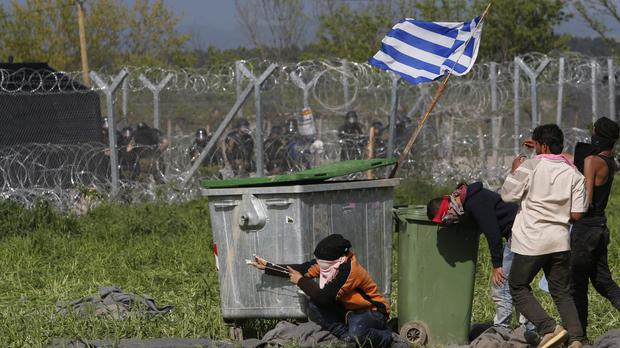 A group of migrant men throw rocks during clashes with Macedonian police during a protest at a fence at the northern Greek border point of Idomeni (AP)