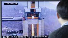 A man in Seoul watches a TV news programme showing an image reportedly of a North Korean ground test of a new type of high-thrust rocket engine (Ahn Young-joon/AP)