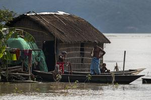 A family takes shelter on a boat near their partially submerged house in Assam, India (Anupam Nath/AP)