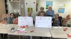 Care home residents hold posters reading 'Thank you for everything' in Corbas, central France (Valerie Martin via AP)