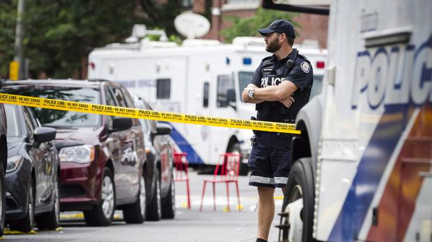 Police watch the perimeter of the scene of a mass shooting in Toronto (Christopher Katsarov/The Canadian Press/AP)