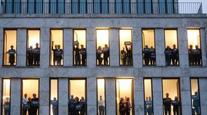 Employees of German news magazine Der Spiegel hold posters in tribute to the people killed at Paris offices of weekly newspaper Charlie Hebdo