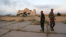 Iraqi security forces and allied Shiite militiamen stand guard in front of one of Saddam Hussein's palaces in Tikrit (AP)