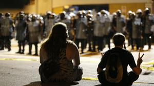 Police and protesters square off outside the Richmond Police Department headquarters on Grace Street in Richmond, Va., Saturday, July 25, 2020. Police deployed flash-bangs and pepper spray to disperse the crowd after a city utility vehicle was set on fire. (James H Wallace/Richmond Times-Dispatch via AP)