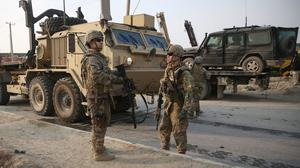 US and British soldiers talk at the site of a suicide car bomb attack in Kabul (AP)