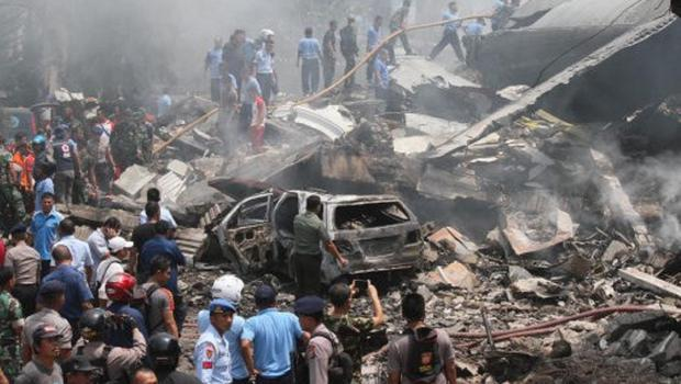 Firefighters and military personnel inspect the site where an air force cargo plane crashed in Medan, Indonesia (AP)