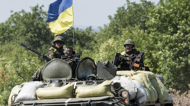 Ukrainian government troops sit atop of their military vehicle in the Donetsk region (AP)