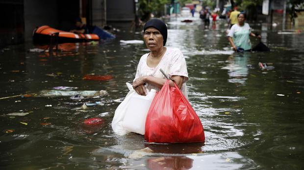 A woman wades through flood water in Jakarta (Dita Alangkara/AP)