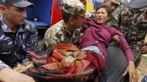 A woman who suffered two broken legs in Saturday's massive earthquake arrives by helicopter from the heavily-damaged Ranachour village at a landing zone in Gorkha, Nepal (AP)