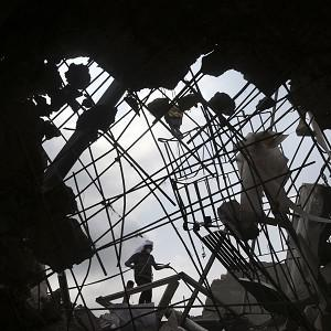 A worker is seen through a broken cement wall as he toils in the collapsed garment factory building in search of bodies (AP)