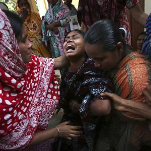 A woman is comforted by family members after she identified the body of her relative recovered from the rubble of the garment factory (AP)