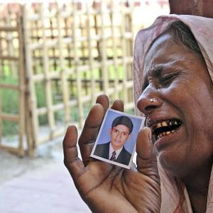 A Bangladeshi woman weeps as she holds a photo of her son, missing in the building collapse (AP)