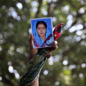 A woman holds up a portrait of her missing relative in Savar, near Dhaka, Bangladesh (AP)