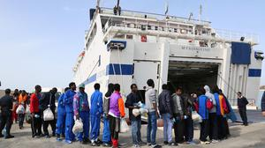 Migrants board a ferry on the Island of Lampedusa, southern Italy (AP)