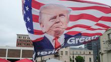 Rallying: A man parades along the street in Tulsa carrying a flag with the image of Donald Trump on it. Photo: Matthew Hatcher/Bloomberg