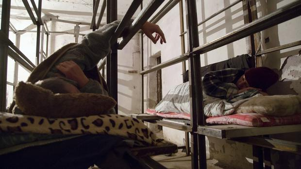 A couple sleep in a bomb shelter as they hide from night shelling in the Petrovsky district in Donetsk (AP)