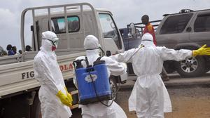 Health workers spray each other with disinfectant chemicals as they work with a suspected Ebola virus death in Liberia (AP)