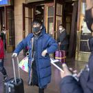 Travellers wear face masks as they walk outside of the Beijing Railway Station in Beijing (Mark Schiefelbein/AP)