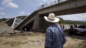 A man stands by the collapsed Aduano bridge leading to Los Cabos, Mexico, that fell several days after Hurricane Odile hit the region (AP)
