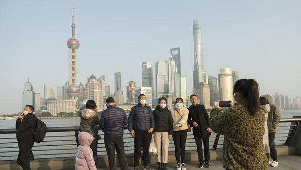 Visitors wearing protective face masks pose for a photo along the Bund in Shanghai (AP)