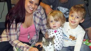 Scarlette, centre, and her family meet amputee kitten Holly (Riverside County Department of Animal Services/AP)
