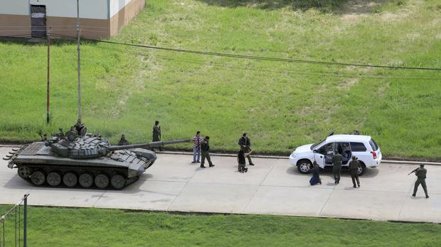 Soldiers stop a vehicle, whose passengers kneel on the ground outside the car, at the Paramacay military base in Valencia (AP Photo/Juan Carlos Hernandez)