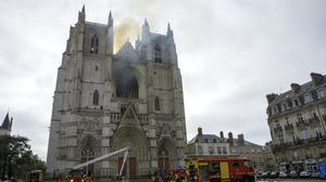 Firefighters work to extinguish the blaze at the Gothic St Peter and St. Paul Cathedral in Nantes, western France (Laetitia Notarianni/AP)