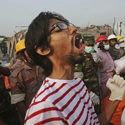 A Bangladeshi rescue worker shouts as others remove the body of a worker (AP)