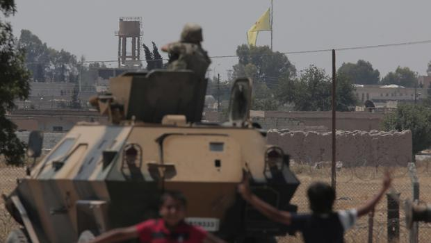 A Turkish soldier on an armoured personnel carrier watches while in the background a flag of the Kurdish People's Protection Units, or YPG, is raised over the city of Tal Abyad (AP)